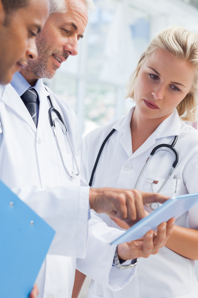 Doctor showing something in his tablet to his medical team